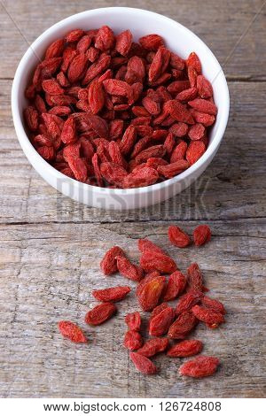 Goji berries in a white  bawl on old wooden board