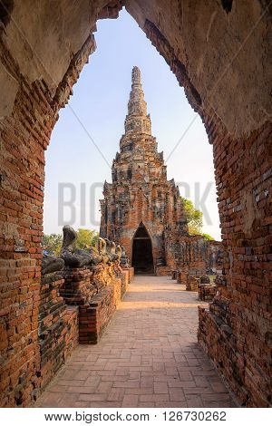 the ancient pagoda in Chai Wattanaram temple in Ayuthaya historical park with the sun set light with the door frame