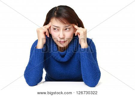 studio shot of Asian woman suffers from headache on white background
