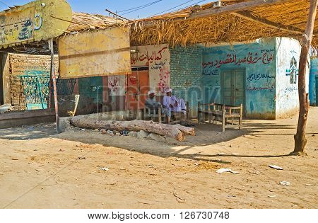AL MAHAMID EGYPT - OCTOBER 7 2014: The elderly Egyptians relax in the shady terrace sitting on the trestle-bed on October 7 in Al Mahamid.