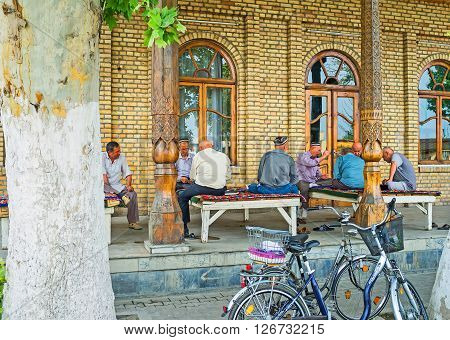 KOKAND UZBEKISTAN - MAY 6 2015: The elderly men spend their time playing cards and sitting on the trestle-beds at the summer terrace of traditional teahouse on May 6 in Kokand.