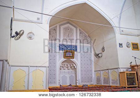 KOKAND UZBEKISTAN - MAY 6 2015: The interior of the mosque located in building of Norbut-biy Madrasah with the white carved mihrab in the middle on May 6 in Kokand.