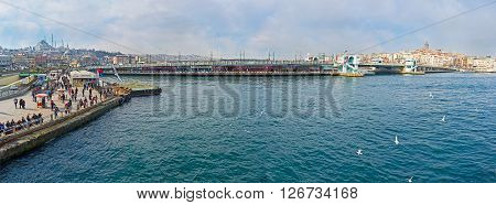 ISTANBUL TURKEY - JANUARY 21 2015: The panoramic view from the ferry on the wide Golden Horn Bay Eminonu promenade and Galata bridge on January 21 in Istanbul.