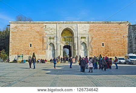 ISTANBUL TURKEY - JANUARY 21 2015: The Royal Gate of Topkapi Palace with the goups of tourists waiting the excursion on January 21 in Istanbul.