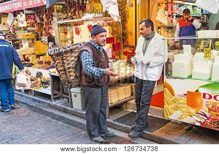 ISTANBUL TURKEY - JANUARY 21 2015: The conversation of the friends - merchant and buyer with the rustic basket on the back next to the cheese stall on January 21 in Istanbul.