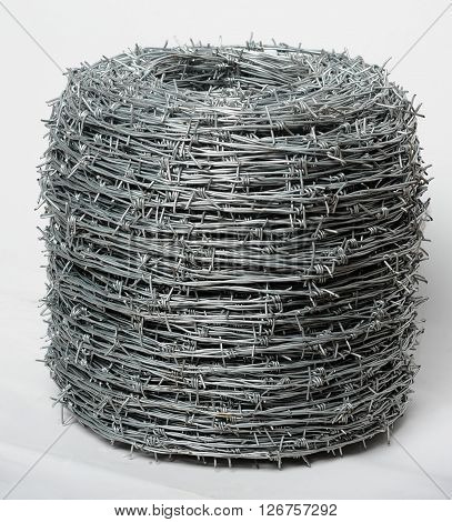 Roll of twisted barbed wire at white background