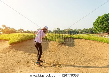 Asain woman golfer hitting golf ball out of a sand trap