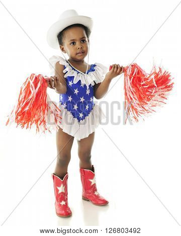 An adorable 2 year old wigging her pom-poms while in her star studded,western red, white and blue outfit.  On a white background.