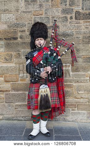 EDINBURGH SCOTLAND - MARCH 8TH 2016: A Scotsman wearing traditional Scottish outfit playing the bagpipes along the Royal Mile in Edinburgh on 8th March 2016.