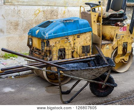working tools for repairing city roads with bitumen and asphalt mix wheelbarrow shovel rake steamroller