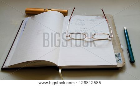 personal note keeping diary and pen with spectacles