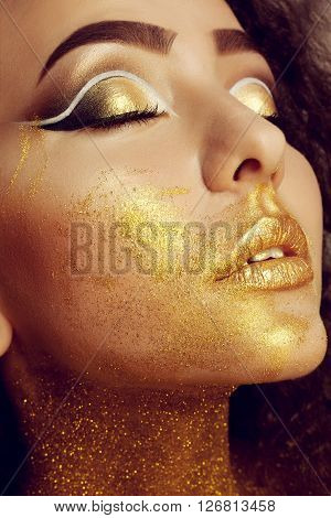 Magic Girl Portrait in Gold. Golden Makeup close-up portrait in studio shot color closed eyes