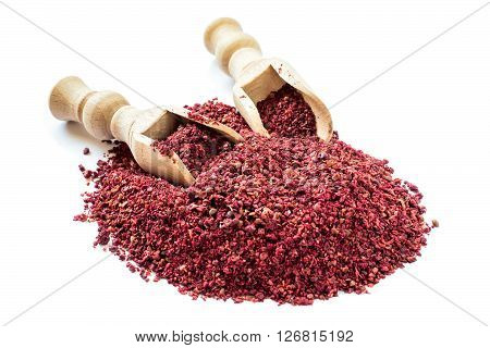 Popular eastern spice sumac in a scoop on a white background