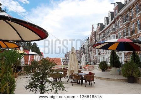 Kemer, ANTALYA, TURKEY - MAY 30, 2015: Street with original buildings and colored umbrellas in hotel Orange County Resort, Turkey.