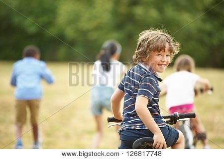 Interracial kids with mountainbike and scooter at the park