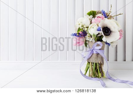 Bouquet from pink tulips violet grape hyacinths white anemones violet veronica and white buttercup with violet ribbon on white wooden shutter background
