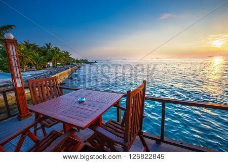 Beautiful sunset from restaurant on the beach. Tropical island with sandy beach palm trees and tourquise clear water
