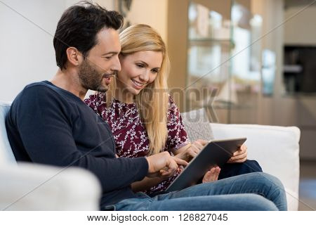 Young happy couple surfing on the web at home. Smiling woman and man checking mail together on tablet. Happy young couple sitting on sofa and working on digital tablet. Shoppin online.
