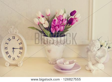 Image of vintage mantel clock a bouquet of tulips and an angel figurine. The image in pastel shades. Fireplace with beautiful decorations in comfortable living room.