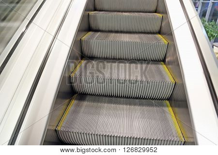 escalator in office with metal steps,horizontal image