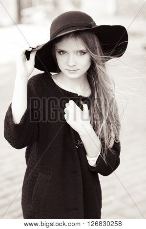 Beautiful girl 14-16 year old wearing hat and black coat outdoors. Black and white image. Fashionable.