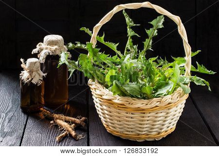 Medicinal plant - dandelion. Dandelion leaves in a basket tincture and syrup in pharmaceutical bottles roots on wooden background. It is used for herbal medicine and healthy food poster