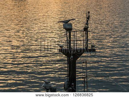 ship's mast of a small vessel against the sea at sunset