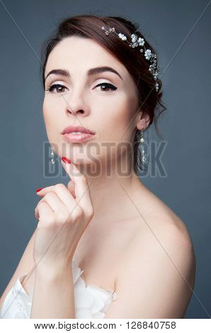 Elegant bride with brown short hair updo and bare shoulders white wedding dress and beaded headpiece in her hair. Headshot.