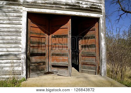 An old weathered shed has a  system of three doors which are deteriorating and left ajar.
