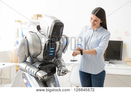 Magic device.  Pleasant content smiling beautiful girl using her smart watch and showing it to the robot who is standing nearby