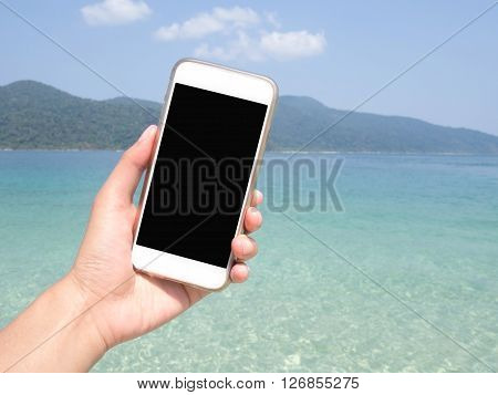 Close up of woman's hand holding smartphone mobile smart phone over blurred beautiful blue sea and clear sky on beach background for working online on vacation. Phone with black screen.