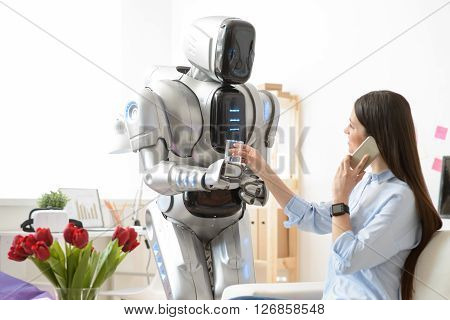 Glad to serve for you.  Smiling modern robot  holding glass of water and giving it to nice charming woman who is sitting at the table and talking on cell phone