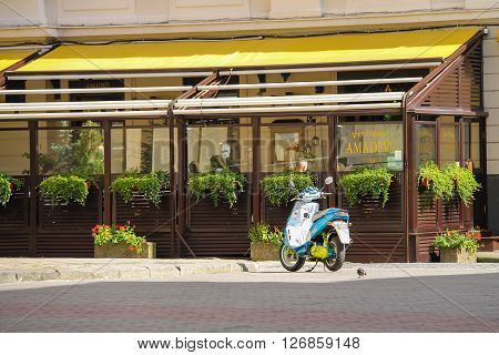 Lviv Ukraine - July 5 2014: Parked moped near outdoor terrace of restaurant Amadeus in historic city center