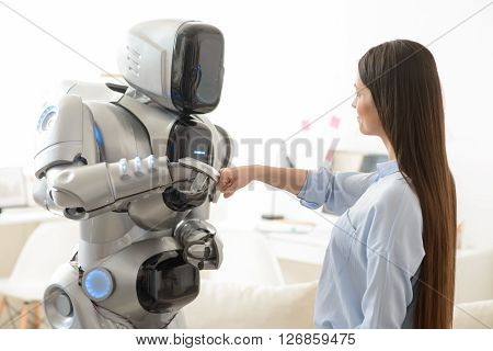 Happy to work together.  Pleasant positive girl and modern robot holding their hands in fists and holding them together while expressing gladness