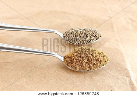Healthy food cumin powder and seeds in steel spoons on a brown paper background.