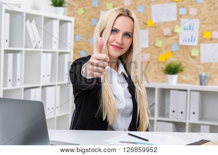 Pretty businesswoman smiling and showing thumbs up in office