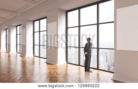 Interior design with wooden floor blank posters on columns and businessman looking out of window with New York city view. Mock up 3D Rendering