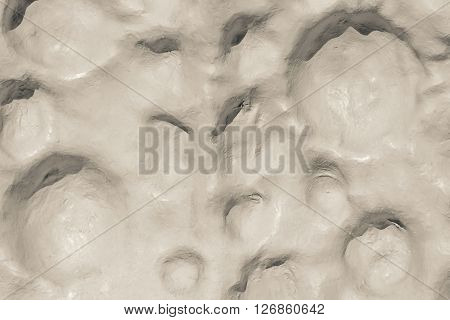 the abstract textured background of a bumpy surface of beige color