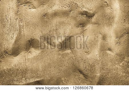 the abstract textured background of a bumpy surface of bronze sand color