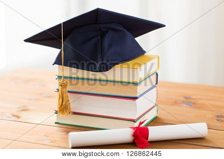education, school, graduation and knowledge concept - close up of books and mortarboard with diploma on wooden table