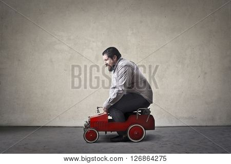 Chubby man driving toy car