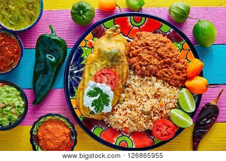 Chili relleno chili pepper poblano filled with cheese in dish with with rice and frijoles beans