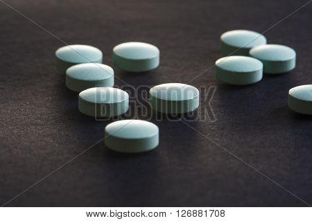 Blue medicine pills on black background. Pharmaceutical medicament. Macro.