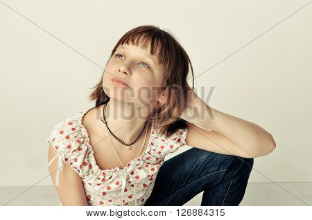 Portrait of the girl - teenager. Girl sits with one leg bent.