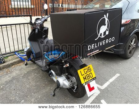 LONDON - APRIL 21: A parked Deliveroo food delivery scooter on April 21, 2016 in West Hampstead, London, UK.