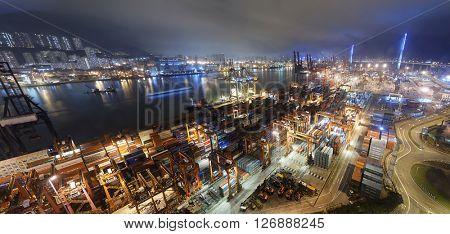 Cargo ship and crane at port reflect on sea bay, hong kong twilight time