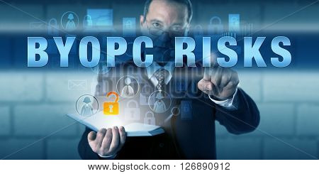 Human resources director is touching BYOPC RISKS on an interactive visual screen. Corporate workplace trend metaphor and information security concept for Bring Your Own Personal Computer risks.