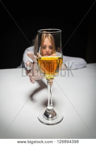Young beautiful woman in depression drinking alcohol on dark background