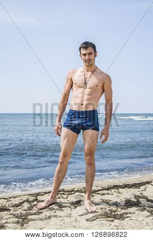 Brutal man all wet came from the water. A man stands on the shore of the warm sea.