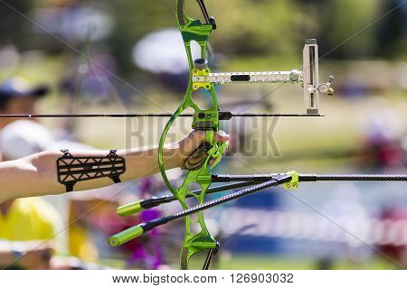 Person is shooting with recurve bow during an archery competition. Hand and bow only. Green bow. poster